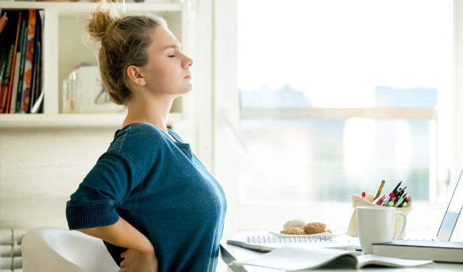 Woman with back pain at table