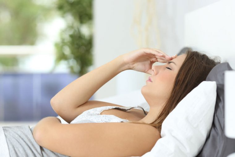 Woman lying down with migraine headache
