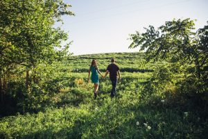 Couple walking through a field together