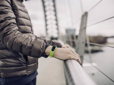 Woman wearing Fitbit on bridge in London