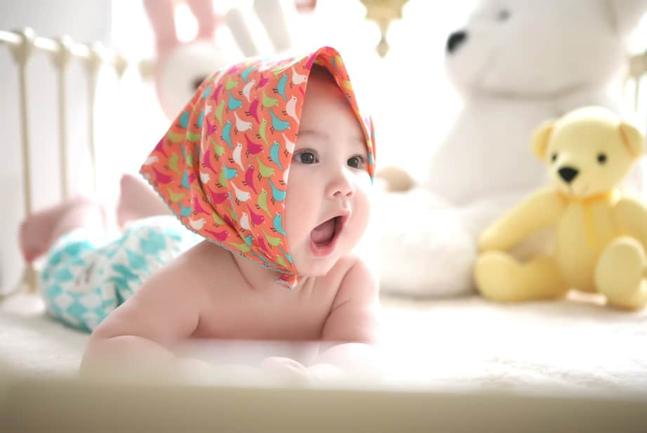 Baby in cot wearing hat